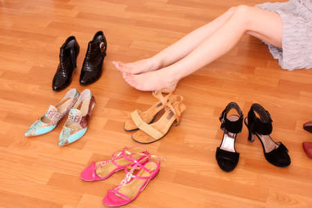 female soles: Closeup of a woman leg on floor and many shoes around