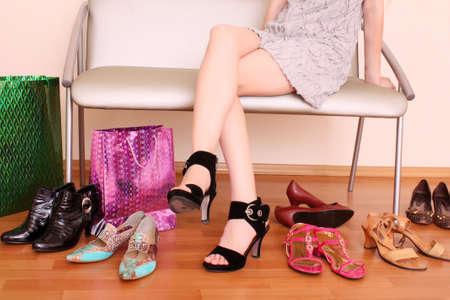 comprando zapatos: Mujer joven tratando de zapatos nuevos en una tienda.  Foto de archivo