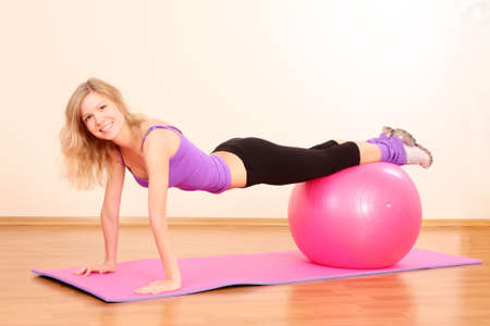 Young beautiful fitness girl with pink ball exercising in the gym photo