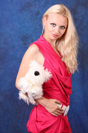 Beautiful blond girl in pink dress with small dog  on blue photo