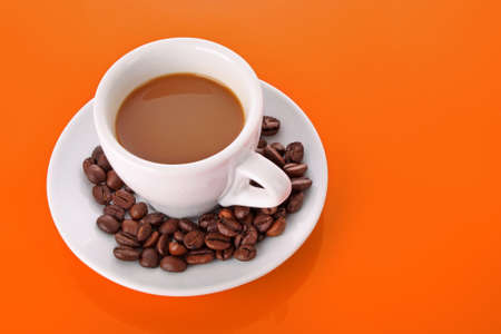 Small white cup of coffee with coffee grain on orange background photo