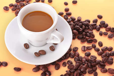 Small white cup of coffee with coffee grain photo