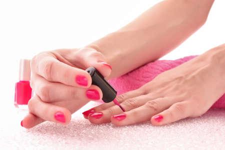 nail polish bottle: Woman applying pink nail polish Stock Photo