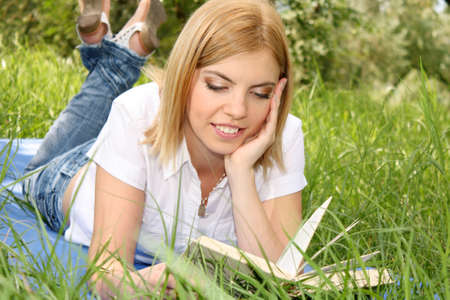 Portrait of young blonde woman reading book in the  park photo