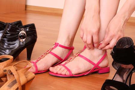 comprando zapatos: Joven tratando de zapatos nuevos en una tienda  Foto de archivo