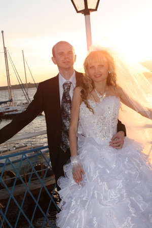 Just-married couple on the sunset background photo
