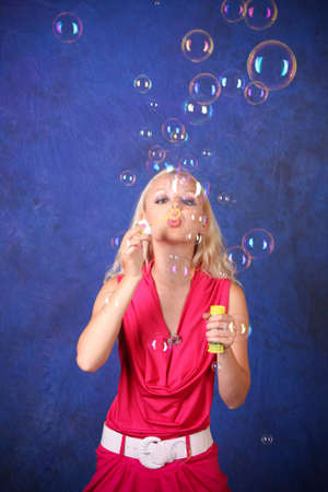 Beautiful young woman blowing soap bubbles on blue photo