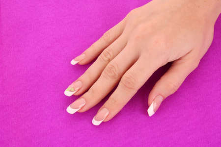 Beautiful woman hands with french manicure on pink background photo