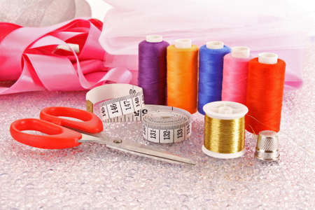 needle, threads, scissors, ribbons  and measuring tape photo