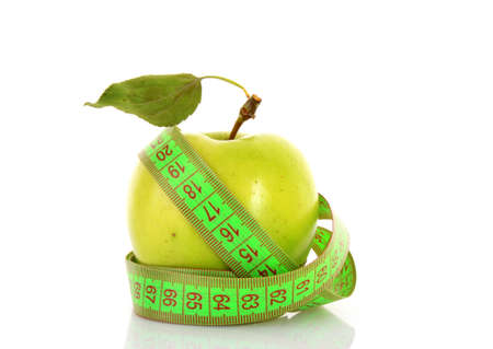 Green apple and tape measure close up photo