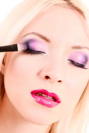 Beautiful young blonde woman with bright make-up and brush  on white photo