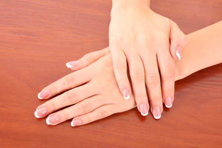 Beautiful woman hands with french manicure on brown background Stock Photo - 8081634