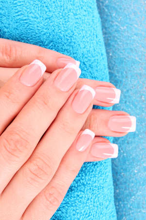 nail care: Beautiful woman hands with french manicure on blue background