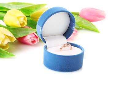 Anello di fidanzamento oro nella casella sullo sfondo fiori