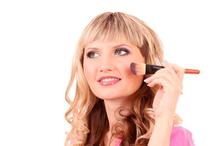 Beautiful young blonde woman applying  blusher photo