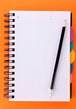 Notebook with pencil on the orange background Stock Photo - 8253170