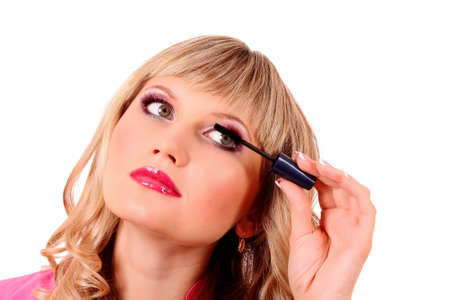 Beautiful young blonde woman applying mascara on her eyelashes photo