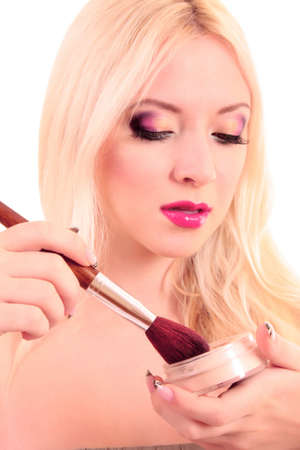 Portrait of attractive young blonde woman applying blusher photo