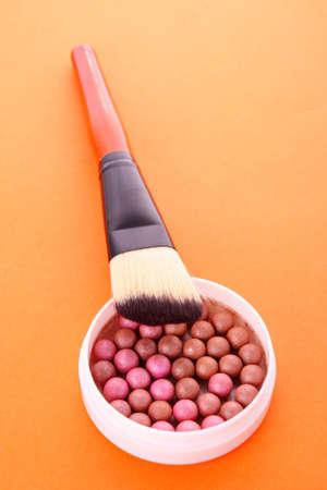cosmetic brush and rouge  on the orange background photo