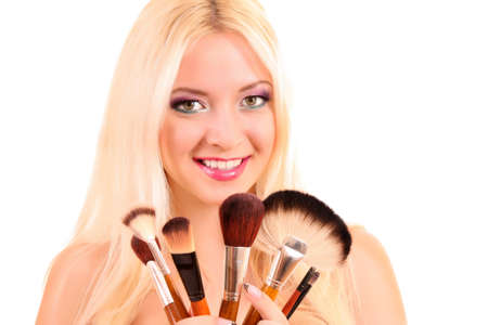 Beautiful young blonde woman with bright make-up and many brushes  on white photo