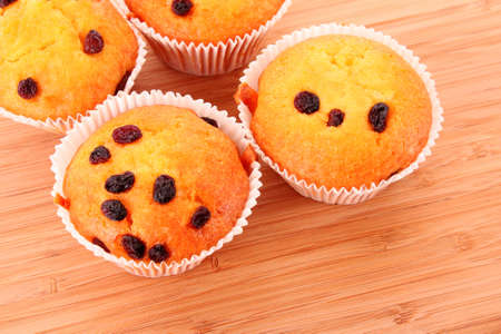 Muffins with raisins on wooden surface photo