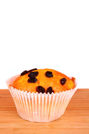 Muffin with raisins on wooden surface isolated on white photo