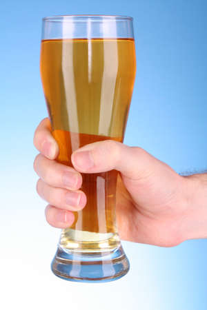 Cup of beer in hand on blue background Stock Photo - 8331504