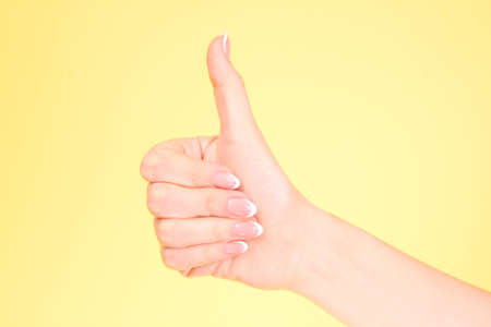 Gestures of hands - OK, on yellow background Stock Photo - 8331535