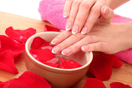 Hands with french manicure  relaxing in bowl of water with rose petals. Stock Photo - 8331616