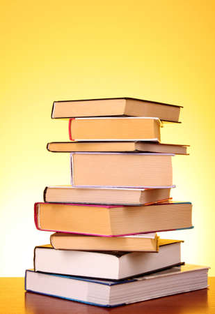 Books pile on the table and yellow background photo