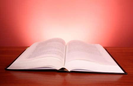 historias biblicas: Gran libro abierto sobre fondo rojo Foto de archivo