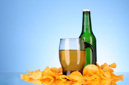 Bottles with beer, cup and potato chips on blue background Stock Photo - 8413542