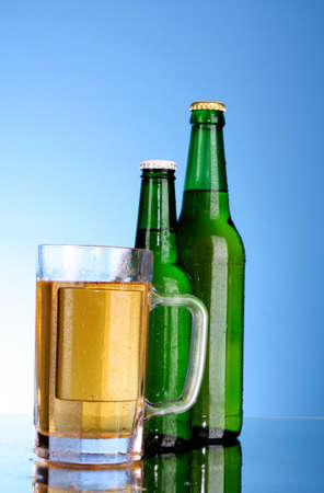 Bottles with beer and cup on blue background photo