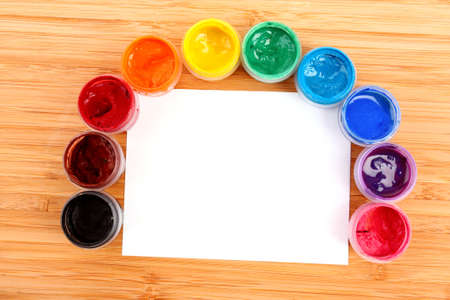Opened paint buckets colors and paper on the table photo