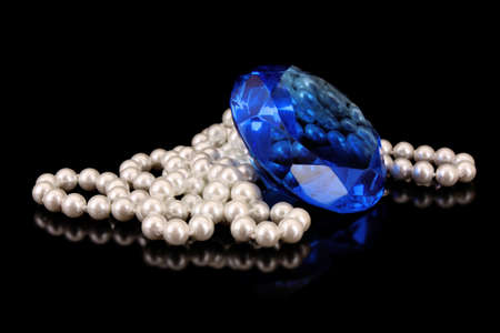 White pearls with big blue gem on black photo