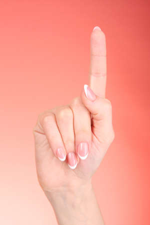Women hand with forefinger up on the red background photo
