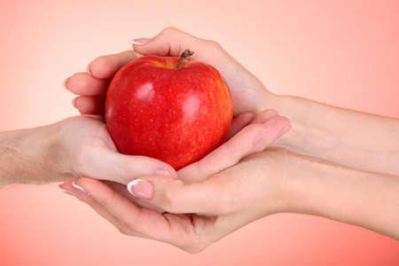 Woman and man hands holding an apple on red background photo