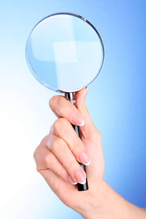 Woman hand with magnifier on blue background Stock Photo - 8463342