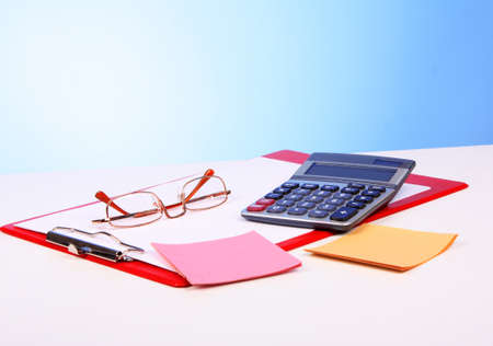 Glasses, calculator and paper on table photo