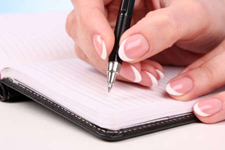 woman hand writting in the notebook on table photo