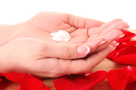 Pair of woman hands holding some cream in the rose petals photo