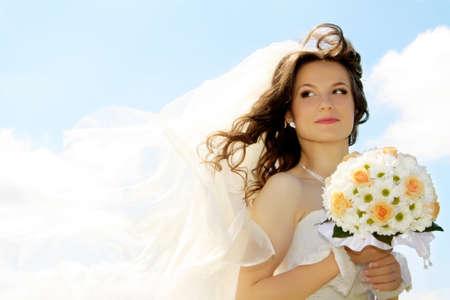 Mooie bruid met zwaaien sluier buiten op haar trouw dag