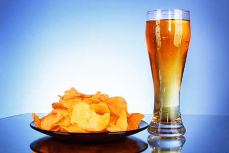 Beer and potato chips on blue background Stock Photo - 8514553