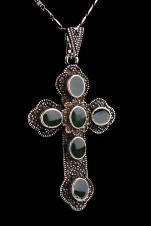 Silver cross as pendant with jewels isolated on black photo