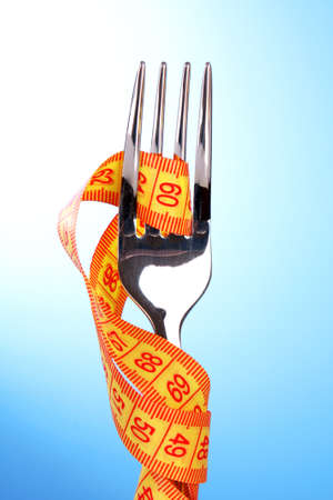fork and measuring tape on blue background Stock Photo