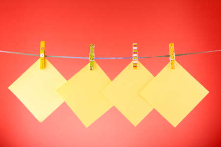 Blank paper sheets on a clothes line against the red background Stock Photo - 8665255
