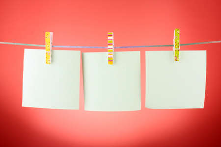 Blank paper sheets on a clothes line against the red background Stock Photo - 8665270