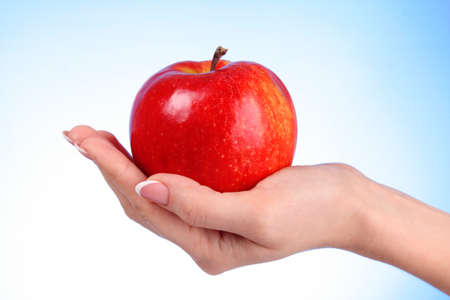 woman apple: An apple on the hand on blue background
