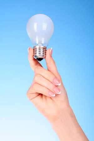 mano con lampadina su sfondo blu