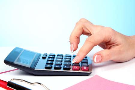 multiplicar: Los dedos y calculadora sobre fondo azul Foto de archivo